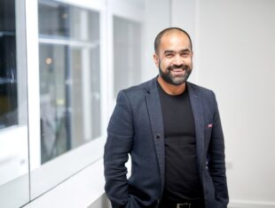 Photograph of a South Asian man in his 40s with a trimmed beard, short hair, wearing a suit jacket
