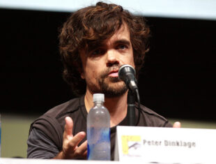 A photograph of actor Peter Dinklage speaking on a panel, he is sat at a microphone.