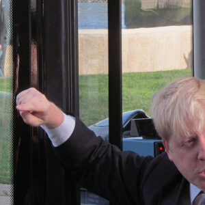 A photograph of Boris Johnson with his hand raised, pulling a stupid face