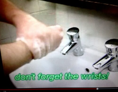 photo of hands being washed above a sink