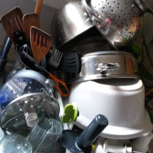 Pots, pans and utensils piled high on a draining board.
