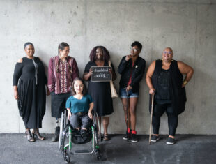 Photo of six disabled people of color smiling and posing in front of a concrete wall.