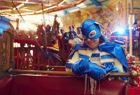 A photograph of Jess Thom as Touretteshero in a superhero costume on a carnival ride.