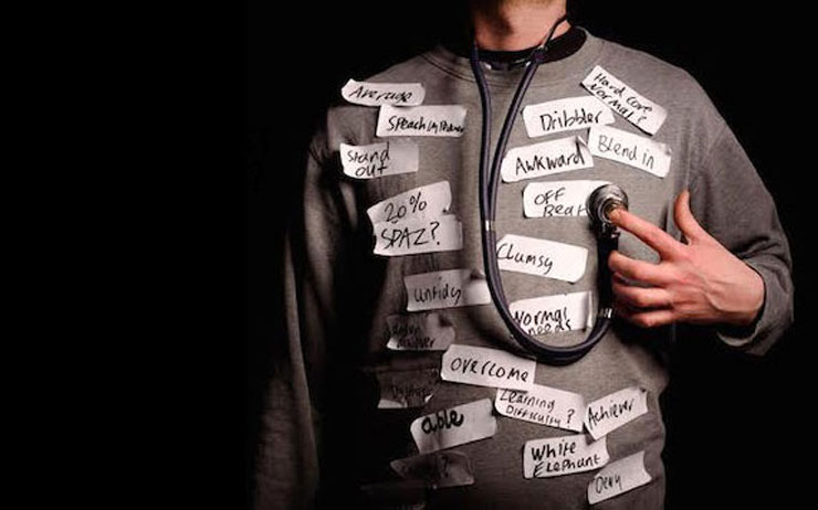 An image of the torso of a man sporting a variety of labels such as 'average', 'awkward', 'dribbler', 'overcome'. He wears a stethoscope attached to his chest