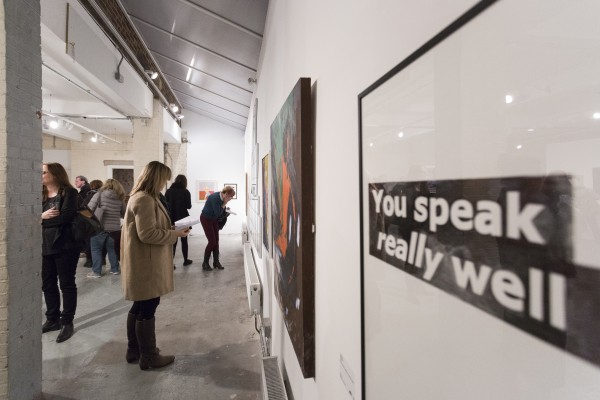 """An exhibition shot from Shape Open 2016, a text based work in the foreground reads """"You speak really well"""". Onlookers admire other pieces on the wall."""
