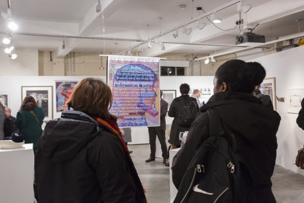 A photograph of two people admiring a piece of art from the Shape Open 2016 exhibition that hangs from the ceiling. Other artworks can be seen around the room, with lots of people walking around.