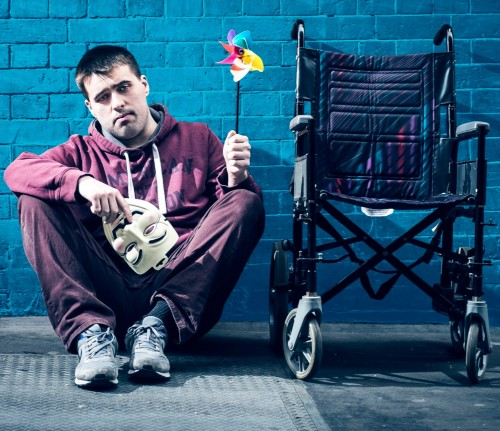 A promotional shot from Access All Areas' Misfit Analysis. It depicts a man sat next to a wheelchair holding a toy windmill and an anonymous mask.