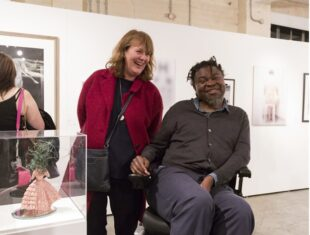 A photograph of artist Yinka Shonibare with Kate Murdoch after she was just awarded the Shape Open 2016 prize. They are standing next to her sculpture Bad Head Day.