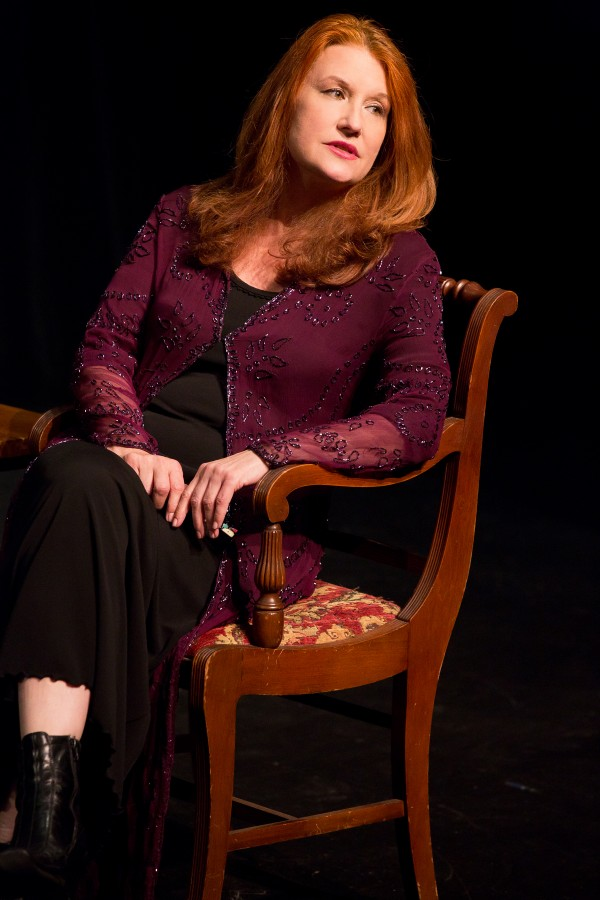 Performance artist, Karen Finley performing Written in Sand. She's sitting in a chair as she talks to the audience who are out of shot.