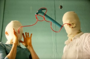 two heads enshrouded in bandages are connected by a red, plastic chord, with a suspended blue hammer
