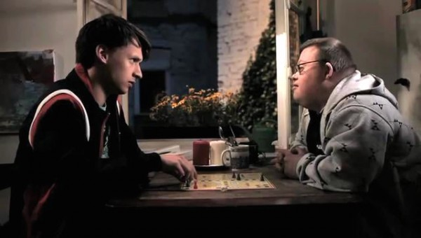 A still from the film 46/47 showing two men facing each other across a table