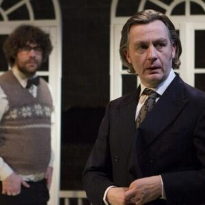 Actor Alan Cox dresses in a smart suit, looking askance as James Russell approaches from behind