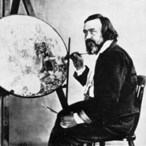 A black and white photograph of Richard Dadd. He is seated and holding a paint brush. In front of him is an unfinished, circular painting on an artist's easel.