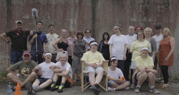 the cast and crew from A Crack In Everything lined up on set