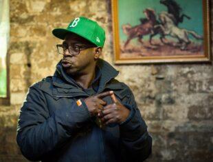 Photo of Film/ TV Director Bim Ajadi wearing a puffa jacket and green baseball cap