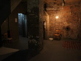 A photograph from theatre company, Bread & Goose's forthcoming production, Siege. It depicts a dank basement area with two chairs and a blanket on the floor, starkly illuminated by a bare light bulb.