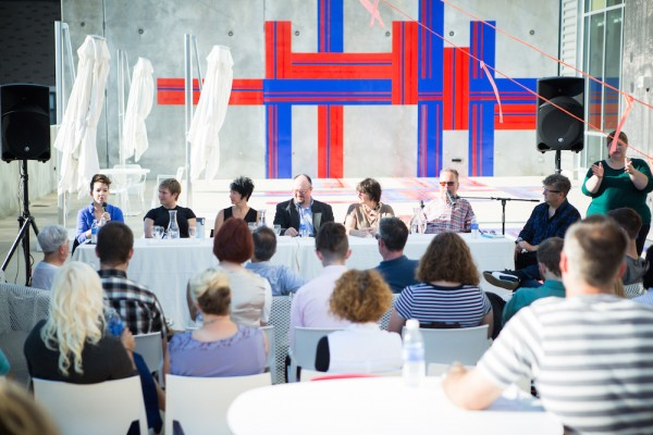 A photograph taken from the City of the Lived Experiment Panel Discussion at UICA. depicting panel members sat at a table in front of a gathered audience.