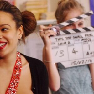 A photograph of two young women attending the BFI's Film Academy, one is holding a clapperboard