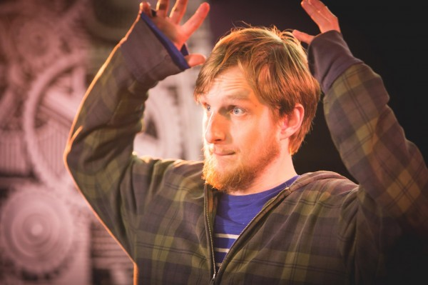 A photograph of writer Jack Dean he is raising his arms either side of his head