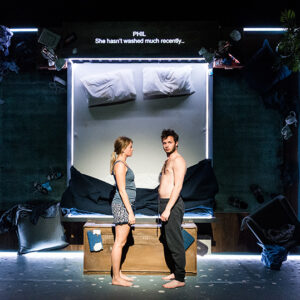 A photograph from the play The Solid Life of Sugar Water. Actors Genevieve Barr (Alice) and Arthur Hughes (Phil) stand in front of a vertical bed which has neon lighting around it.