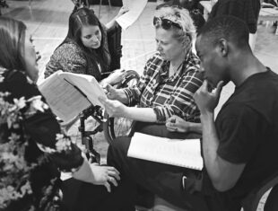 black and white photo of Natalie MacDonald (far left), Amy Conachan, Jenny Sealey and Miles Mitchell in rehearsal