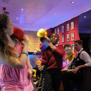 Photo of woman in a pink dress facing a young man who is about to throw a yellow hat in her direction