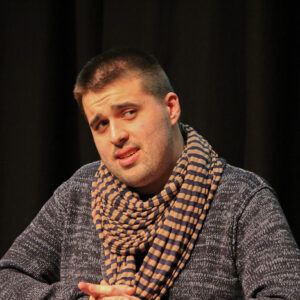 Photo of performer Cian Binchy looking askance in front of the camera