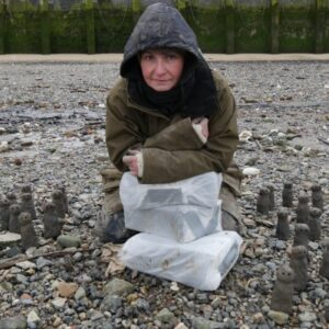 A photograph of artist Liz Crow surrounded by her 'Figures' small clay sculptures resembling people. She is crouched down with a raincoat on.