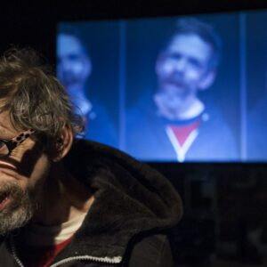Jez Colborne pictured on stage in front of a series of video projections of himself