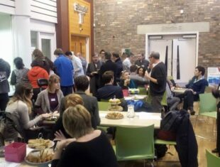 A photograph taken from Mind the Gap's International Learning Disability Live Performance and Touring Event 2015 which shows attendees, some sat round tables, others are standing
