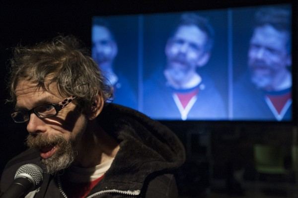 A photograph of Jez Colborne in Mind the Gap's production of Container, he is holding a microphone with projected pictuyres of himself in the background