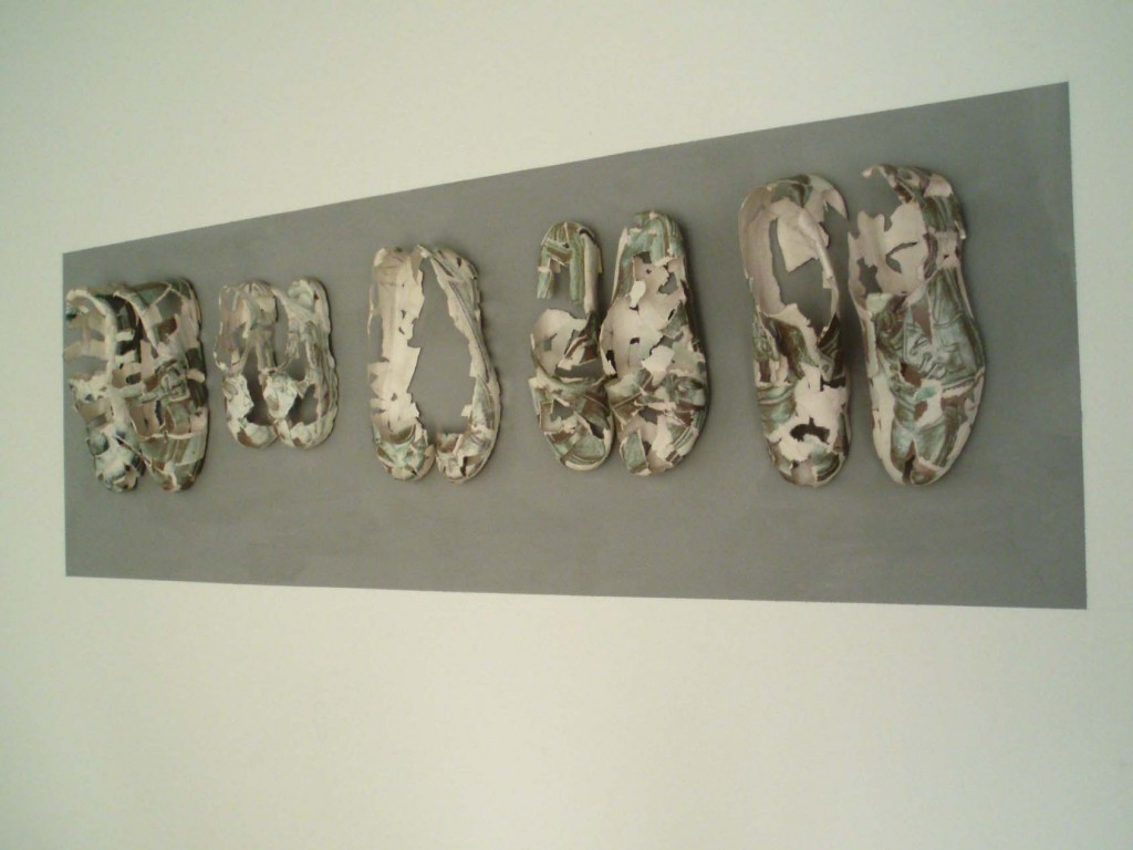 A photograph of Nuclear Family by Anne Teahan depicting 5 pairs of paper shoes made from torn drawings on cartridge paper, wall-mounted on a grey painted rectangle. An installation from 'After Hiroshima' an exhibition at Brunei Gallery SOAS commemorating the 60th anniversary of the bombing of Hiroshima and Nagasaki.
