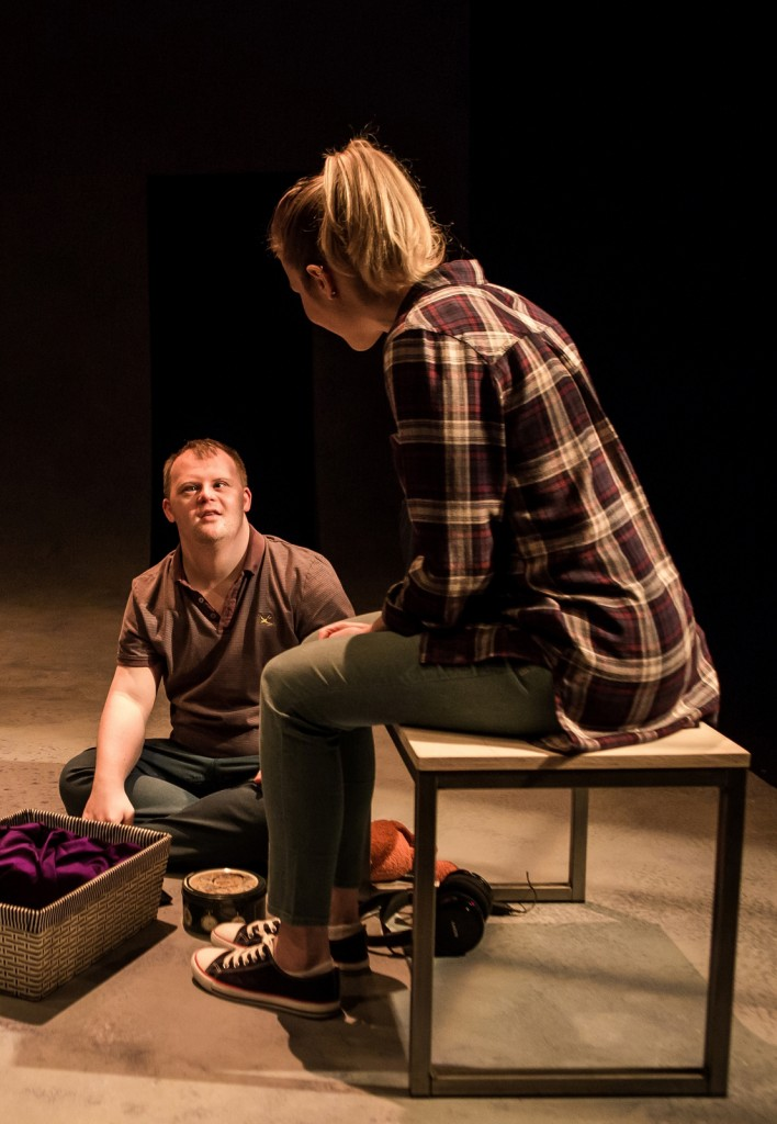 A photograph of Matty (Nathan Bessel) and Darcy (Emily Bowker) from Up Down Man. Matty is sitting on the floor cross legged and Darcy is sitting opposite him, they are in deep conversation.