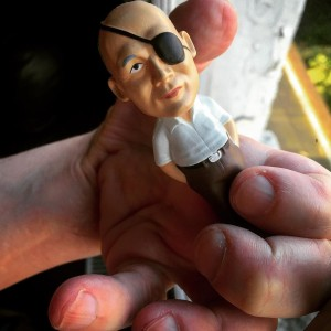 Model of a small figure wearing an eyepatch pictured being held by a pair of hands