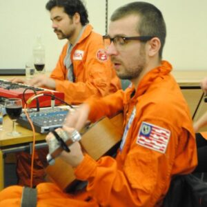 photo of three members of the band Spaceships are Cool playing live wearing orange jumpsuits