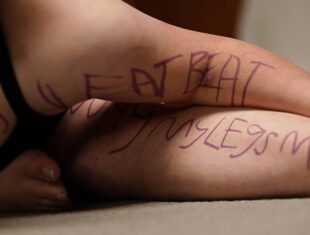 A still from the film Skin Touching Sky showing a dancer crouched down with various words written on her body