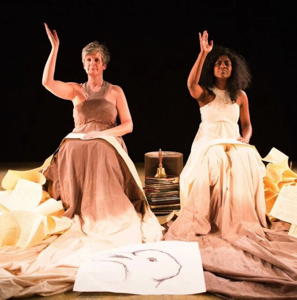 staged photo of two actresses in long dresses, sitting surrounded by reams of paper with a large drawing of a birds head on the floor