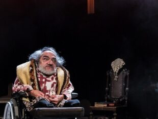 actor nabil shaban has wild grey hair and beard and wears a gold waistcoat playing judge Azdak in Brecht's play