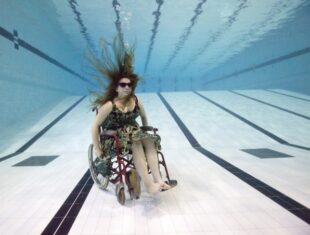 a photo of Trish Wheatley in a wheelchair in an empty swimming pool with her hair splayed outwards