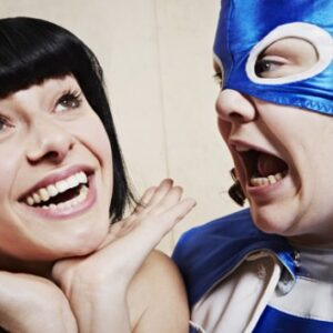 A photograph of Jess Thom and co-performer Jess Mabel Jones. The former has a superhero costume on, the latter has her hands under her chin and is smiling.