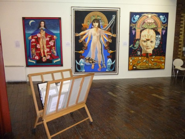 Installation photograph of Yvonne Mabs Francis's three paintings The Bodily Time Machine, Manacles or Bracelets and The Impossibility of Being Inside the Head of Someone Living Menier Gallery