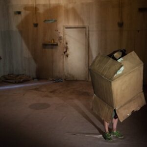 A photograph from Ridiculusmus' production, Give Me Your Love. It depicts a man with a box covering the upper part of his body in a stark room, as a hand creeps around the door.