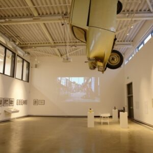Installation shot from Art, Life, Activism, featuring Tony Heaton's Gold Lame hanging from the ceiling, Aaron Williamson's sculptures in the foreground, Noëmi Lakmaier's video projected on the back wall and Bobby Baker's drawings on the right.