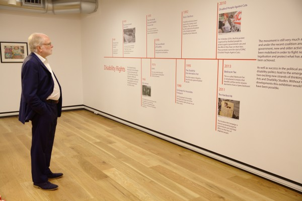 A photography of Michael Attenborough looking at an exhibit on Disability Rights as part of the Art, Life, Activism exhibition.