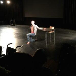 photo of a male dancer on a starkly lit stage, kneeling in front of a chair
