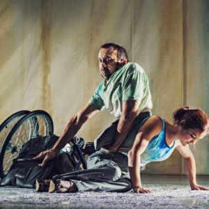 Dancers David Tool and Laura Jones pose on the floor on stage in front of a curtain