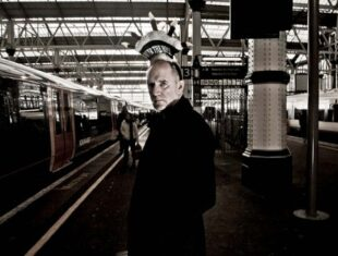A photograph taken from Tim Andrews' Over Hill series. Taken by Roberto Fiddai, it depicts Andrews in a train station with a crown-shaped hat on reading 'over the hill'