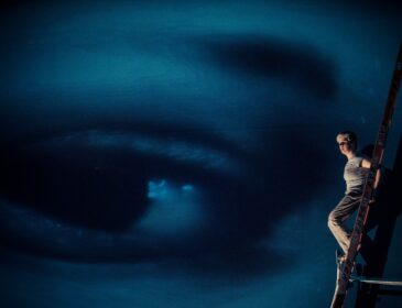 A photograph of dancer Claire Cunningham, she is up a ladder with a huge projection of an eye in the background behind her.