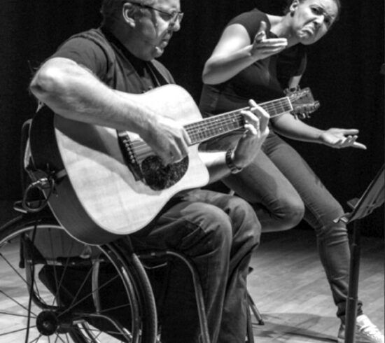 black and white photo of performer Robin Surgeoner sitting with his guitar on stage with a BSL interpreter behind him