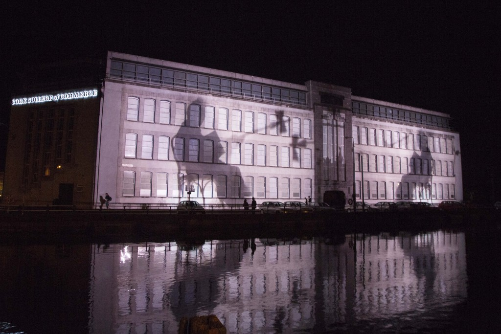 Simon Mckeown's Cork Ignite, featuring a huge project on the facade of a grand building in Cork. It depicts two silhouetted figures sitting in chairs.